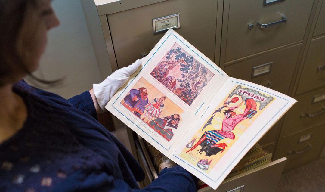 Staff looks at an archival copy of La Chauve-Souris theatrical program